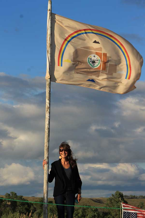 CARRIE BILLY OF AIHEC STANDS WITH NAVAJO NATION FLAG